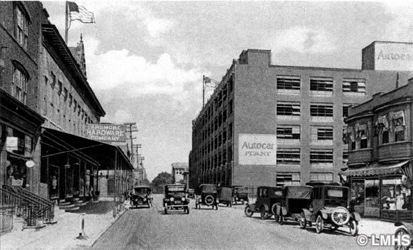 looking up a streetscape with four and five-story buildings and early automobiles