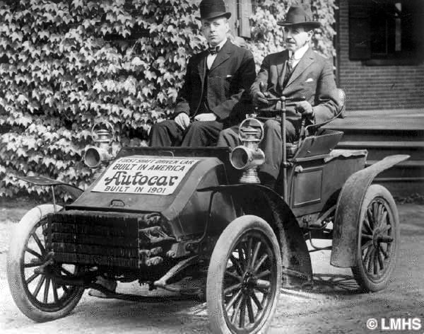 two men wearing suits sit in the single seat of a small early vehicle with a shaft in place of a steering wheel