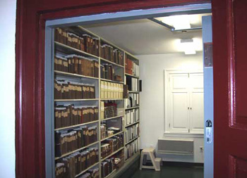 looking through doorway into room with built-in shelves full of books and boxes