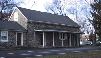 The meeting house, a plain stone building with wooden covered porch