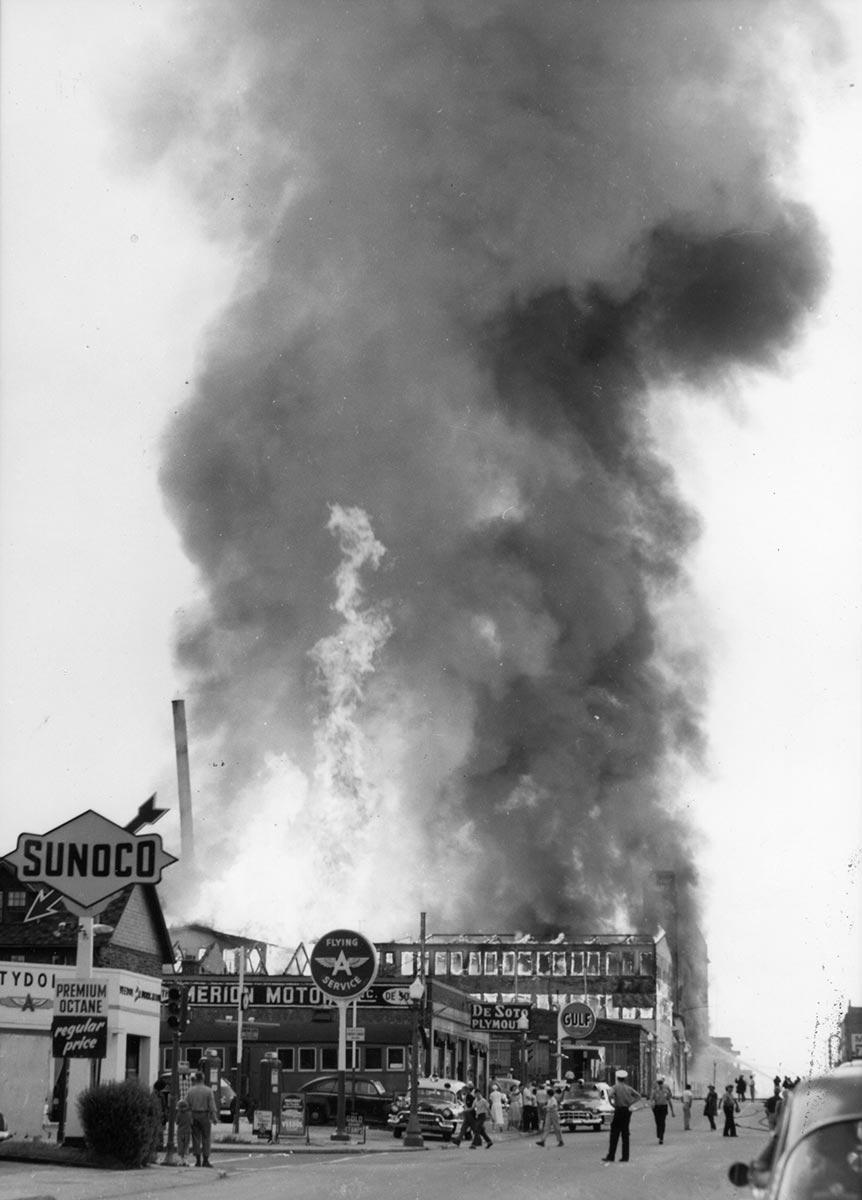 As onlookers watch, a towering blaze and dark smoke fills the sky above a burning 3-story building