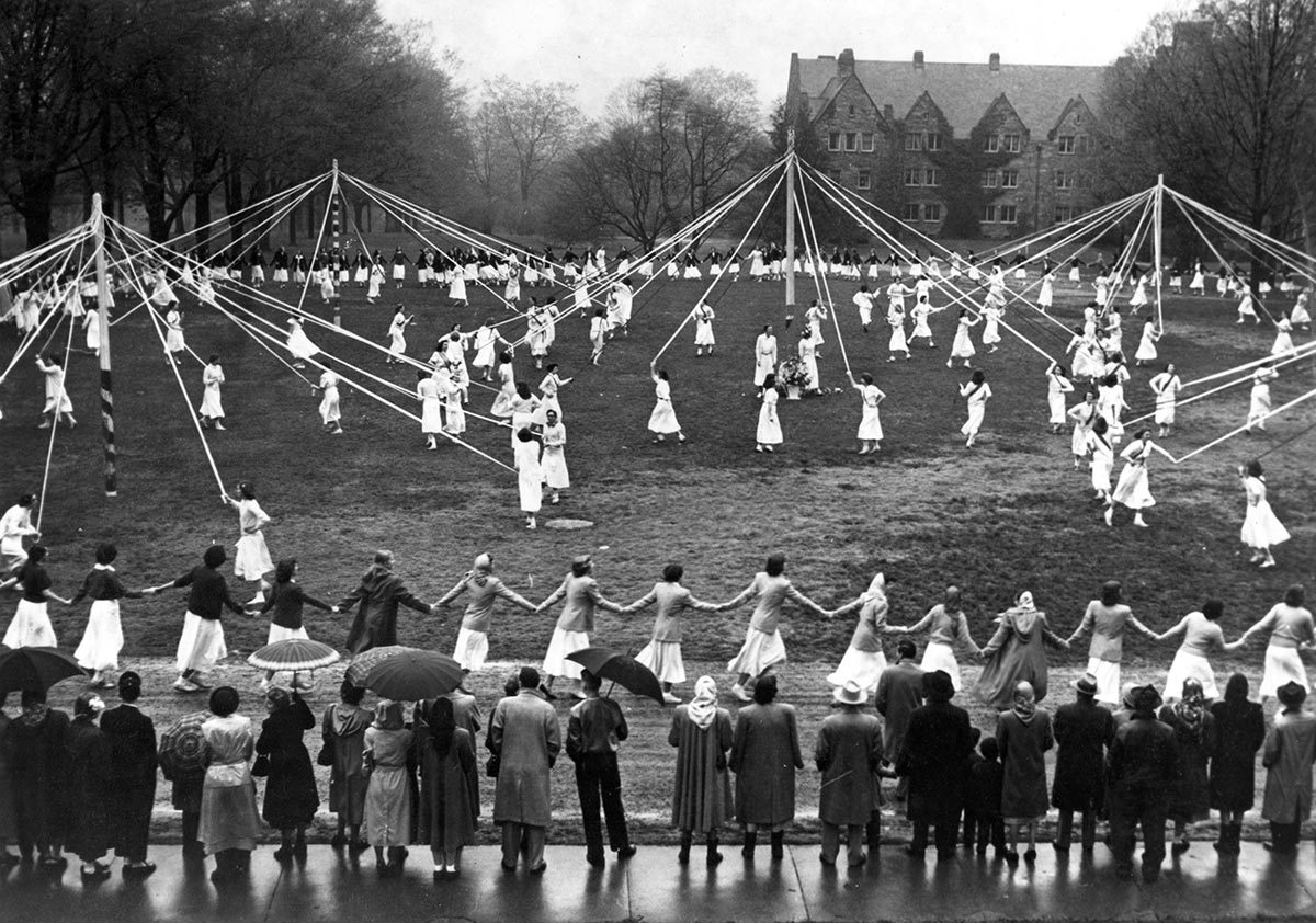 scores of young women dressed in white dance around four maypoles holding ropes tied to the poles' tops; spectators in the foreground