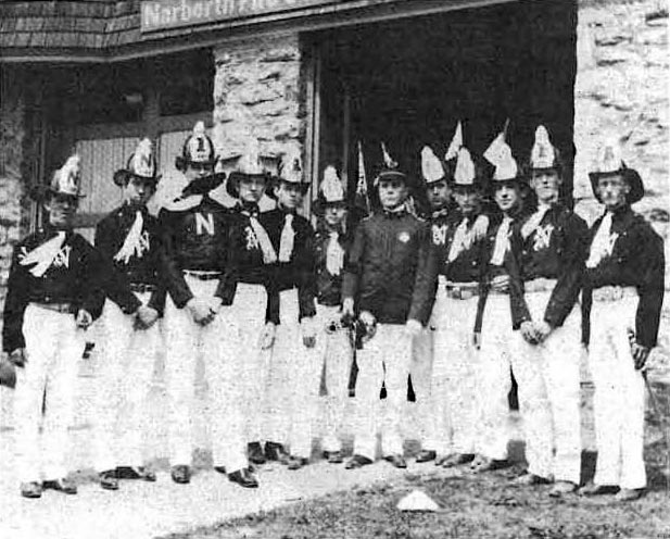 Twelve firemen in dress uniform posed in front of the Narberth fire station