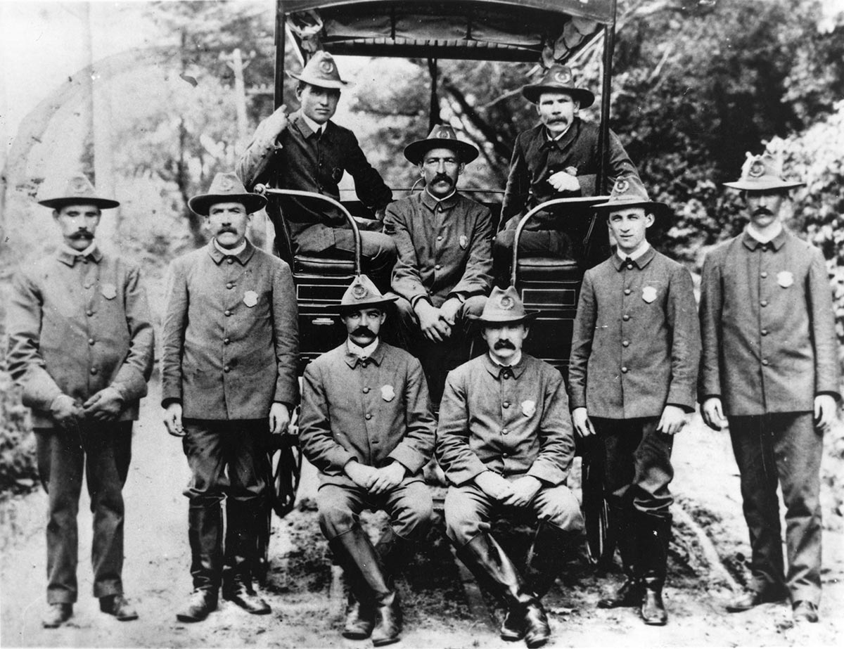 9 uniformed policemen stand in front or sit in early vehicle