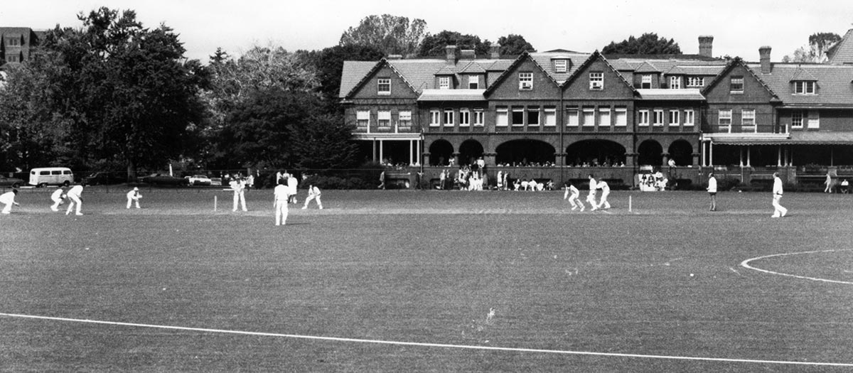 2 teams dressed in white play cricket on a grass field in front an ornate building; spectators watch from its covered porch