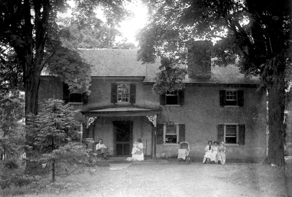 Husband, wife holding a child and three children seated in front of the house