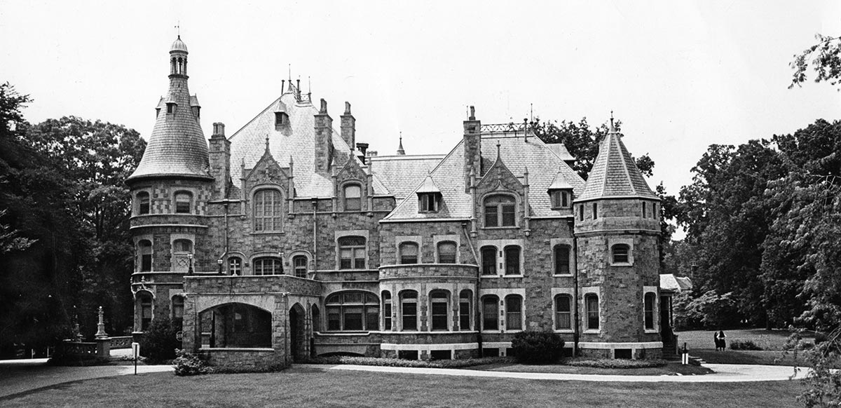 A large ornate stone mansion with turrets and many chimneys
