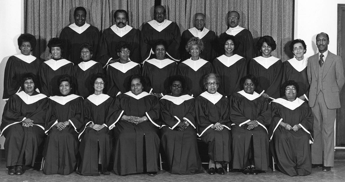 23 African-American singers in choir gowns pose in three rows