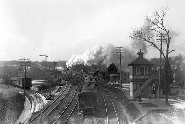 A smoking train pulls past Narberth station heading towards Wynnewood