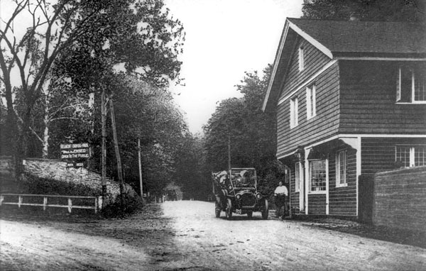A vintage car sits in front of the toll house. The toll keeper stands in front.