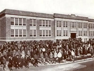 large group poses in front of  school building