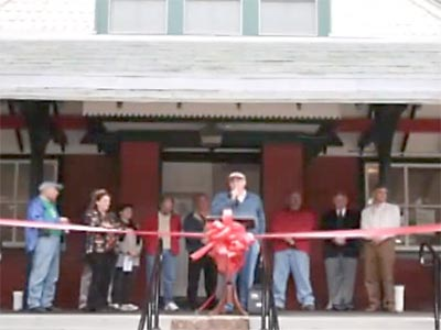 giving a speech on the station porch, group standing behind a ribbon