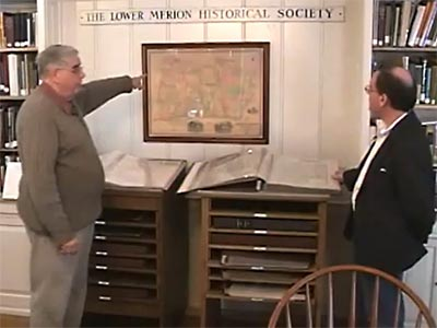 Jerry points to a historical map on the wall