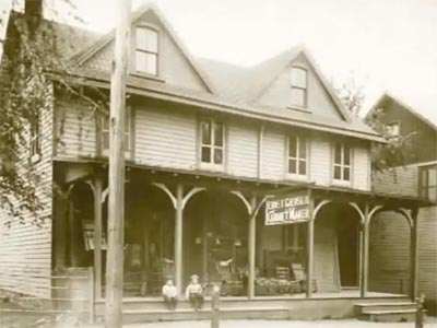 Giersch Cabinet Maker Shop; 2 boys sitting on the front porch