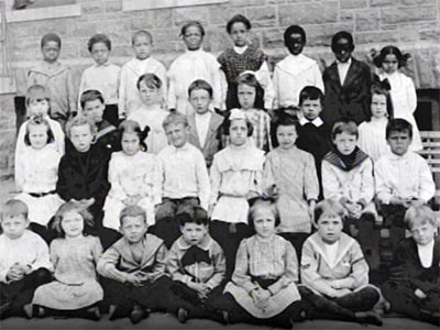 old elementary school class photo, white kids in front rows, blacks separated in the back row
