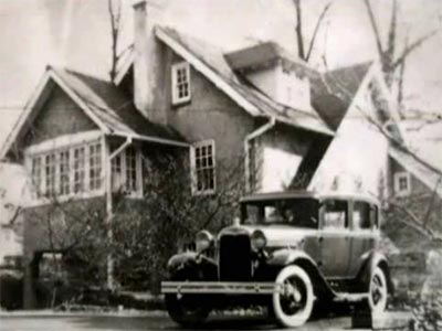 early car in front of a house