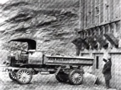 dump truck with 'Rock Hill Quarry' written on side in front of a rock cliff