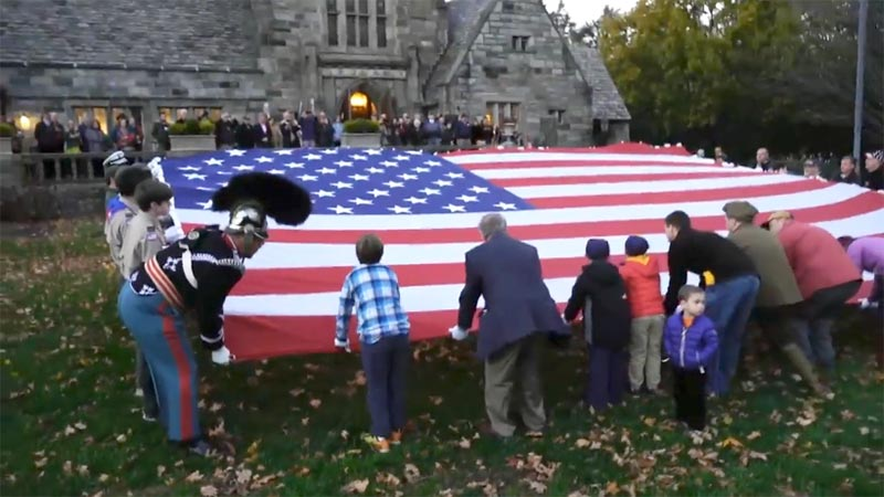 dozens of men, women and children fold a giant American flag at dusk