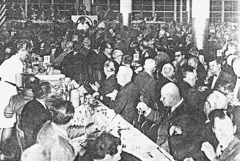 long tables, packed room, men only, in suits and tuxes